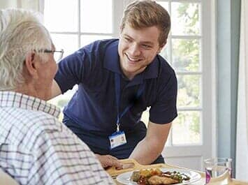 caregiver smiling to senior man