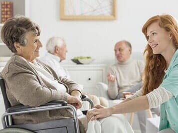 caregiver and senior woman talking with two senior man at their back
