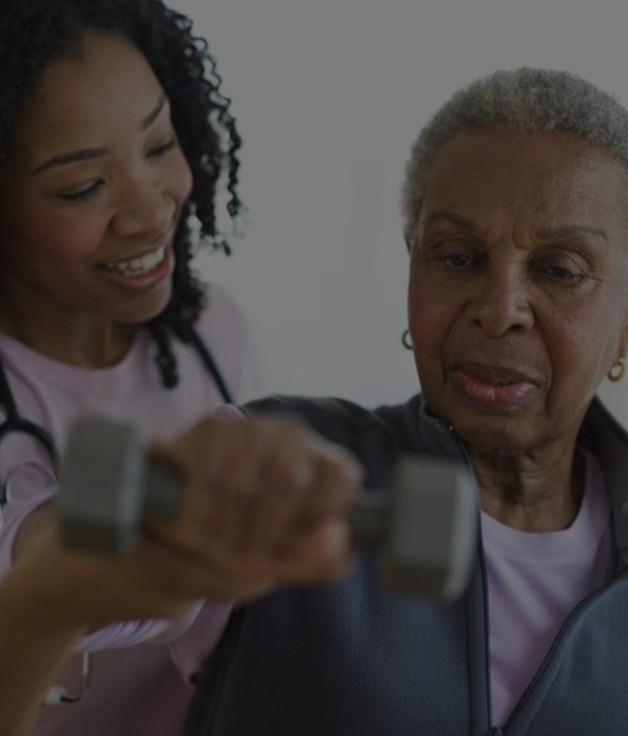caregiver guiding senior woman to do excercise
